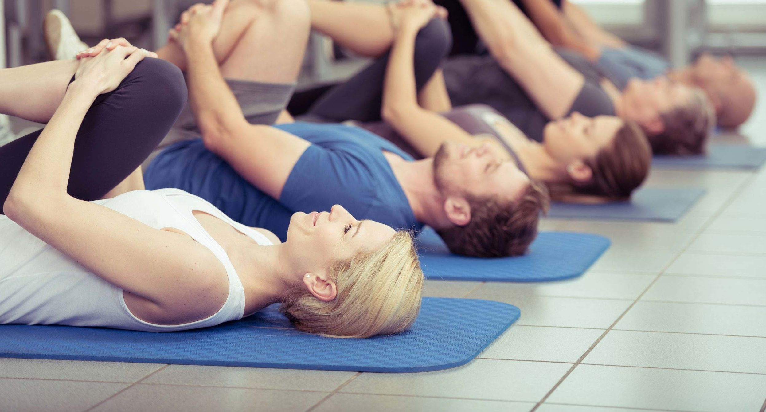 35556071 - diverse group of young and older people exercising at the gym doing leg flexes as they lie on their backs on their mats in a receding row, focus to an attractive young blond girl in the foreground
